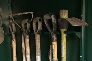 Inside an Asgard metal garden shed with gardening tool rail